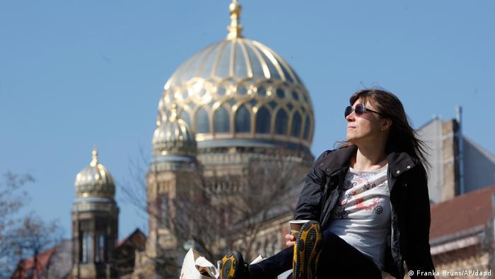 Eine Berlinerin sonnt sich, im Hintergrund ist die Neue Synagoge Berlin zu sehen.(Foto: ddp images/AP Photo/Franka Bruns)