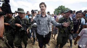 French journalist Romeo Langlois, center, is escorted by rebels of the Revolutionary Armed Forces of Colombia, FARC, upon their arrival to San Isidro, southern Colombia, Wednesday, May 30, 2012. Langlois , who was taken by rebels on April 28 when they attacked troops he was accompanying on a cocaine-lab eradication mission, was handed over by the rebels to a delegation that included a French diplomat in San Isidro. (Foto:Fernando Vergara/AP/dapd)