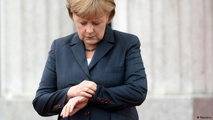 German Chancellor Angela Merkel looks at her wristwatch as she waits for her guests during the arrival for the Council of the Baltic Sea States leader summit in Stralsund, May 30, 2012. REUTERS/Fabian Bimmer (GERMANY - Tags: POLITICS)