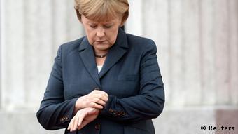 Ангела Меркель смотрит на часы
