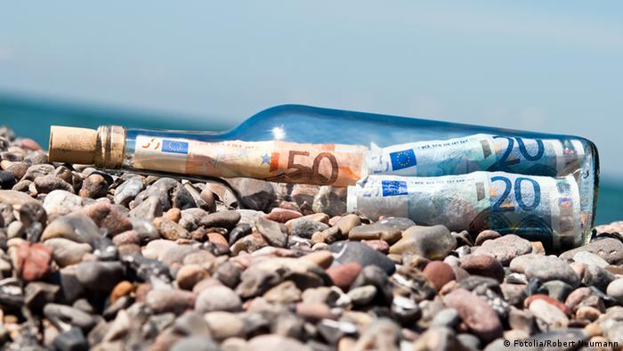 bottle on beach filled with euro bills