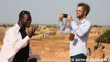 ARCHIV - Der Regisseur Christoph Schlingensief (r) fotografiert neben Francis Kere, dem Architekten des «Operndorfes», in Burkina Faso (Foto undatiert). Der an Lungenkrebs erkrankte Regisseur Christoph Schlingensief (49) ist nach Informationen der Ruhrtriennale tot. Über das Ableben Schlingensiefs habe die Familie die künstlerische Leitung der Ruhrtriennale informiert, sagte am Samstag (21.08.2010) ein Sprecher in Gelsenkirchen auf Anfrage der dpa. Die Familie wolle sich demnächst auf der Webseite Schlingensief.com äußern. Foto: Michael Bogar +++(c) dpa - Bildfunk+++