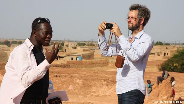 Schlingensiefs Operndorf in Burkina Faso. Man sieht Schlingensief zusammen mit Architekt Francis Kéré auf der staubigen Erde Afrikas.