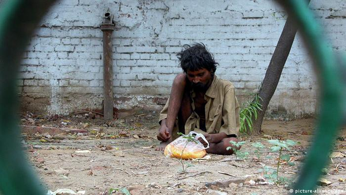 An unidentified person eats on the foothpath in New Delhi, Thursday 24 June, 2004. Most of them are invisible during the daytime and are found only at night, sleeping on the streets, pavements, under flyovers, in parks or open spaces or even on rickshaws. They are the poorest of the poor people who have no shelter or house.Majority of the homeless in Delhi are adults, followed by children and old people. Women, though much less in numbers and generally found in certain locations. The Indian government has been running 12 Raen Basera (night shelters) which accommodates 15000 people. Foto: Money Sharma EPA dpa