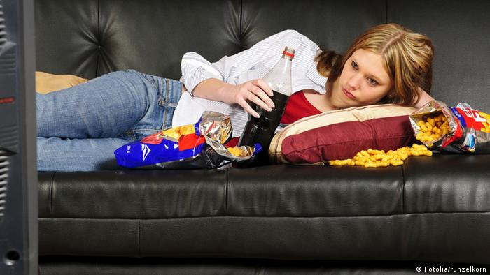 A woman on a couch with food and soda