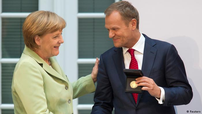 German Chancellor Angela Merkel (L) congratulates Poland's Prime Minister Donald Tusk after he received the Walther Rathenau Prize in Berlin, May 31, 2012. The Walther Rathenau Institute awards annually the Walther Rathenau Prize to people for life achievement in foreign policy. REUTERS/Thomas Peter (GERMANY - Tags: POLITICS)