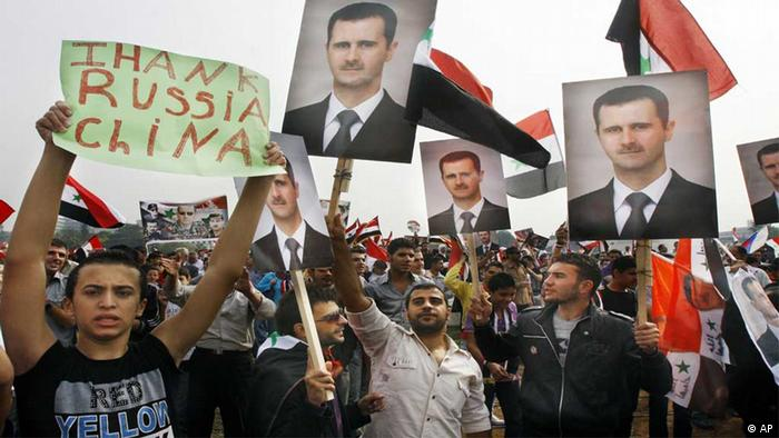 Syrian regime supporters hold up Bashar Assad's portrait and a man holds up a banner that reads Thank China and Russia during a rally in Umayyad Square in downtown Damascus, Syria, Wednesday Oct. 26, 2011. Photo:ddp images/AP Photo/Muzaffar Salman