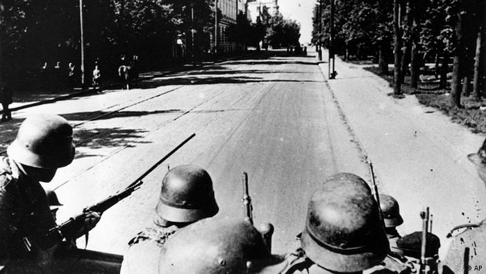 German soldiers, poised with rifle guns, look down a shaded city street in the Soviet city of Kiev, third largest in the country, Sept. 21, 1941, during Nazi occupation in World War II. (ddp images/AP Photo)