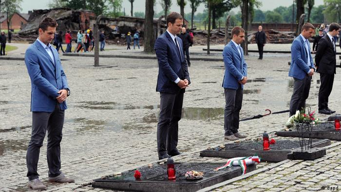 In this photo provided by the German Soccer Federation, DFB, Miroslav Klose, manager Oliver Bierhoff, captain Philipp Lahm and Lukas Podolski, from left, place candles during a visit of the German national soccer team at the Nazi death camp of Auschwitz in Oswiecim, southern Poland, Friday, June 1, 2012. (Foto:DFB, Markus Gilliar/AP/dapd)