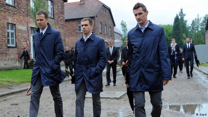 In this photo provided by the German Soccer Federation, DFB, manager Olivier Bierhoff and players Philipp Lahm and Miroslav Klose, from left, tour through the Nazi death camp Auschwitz with the German national soccer team in Oswiecim, southern Poland, Friday, June 1, 2012