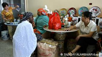 Chinese woman talk business with local women at a shop in Lagos, Nigeria, June 16, 2007. Market stalls are just one of the most visible signs of China's massive penetration into African economies. The Asian giant _ a ready buyer of oil and other raw materials for more than a decade _ is also a major bidder on construction projects, a multi-million-dollar lender and a growing player in Africa's telecommunications and textile industries. (ddp images/AP Photo/Sunday Alamba)