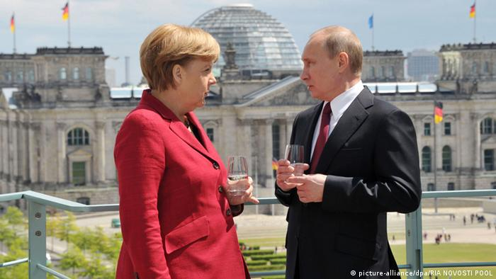 German Chancellor Angela Merkel (L) and Russian President Vladimir Putin (R) speak during their meeting at the Chancellery in Berlin
