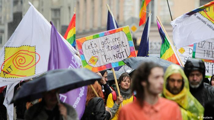 People hold placards and rainbow-colored flags