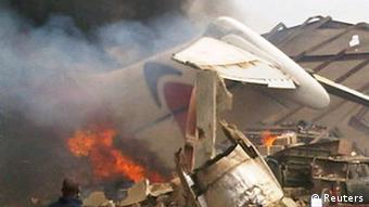 The wreckage of a plane burns in Nigeria's commercial capital Lagos, June 3, 2012. A plane that crashed into a downtown area of the Nigerian city Lagos on Sunday had 147 people on board, a source at the national emergency management agency said. The source said the aircraft belonged to privately owned domestic carrier Dana Air. Two sources at Lagos airport also said the number on board was around 150. REUTERS/Stringer (NIGERIA - Tags: DISASTER TRANSPORT) QUALITY FROM SOURCE