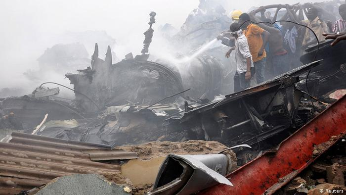 Emergency workers and volunteers hose down wreckage at the scene of a plane crash in Nigeria's commercial capital Lagos