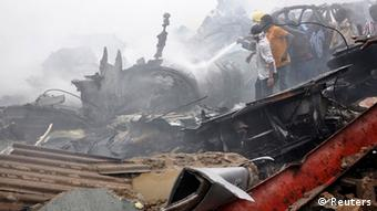 Emergency workers and volunteers hose down wreckage at the scene of a plane crash in Nigeria's commercial capital Lagos, June 3, 2012. A passenger plane carrying nearly 150 people crashed into a densely populated part of Lagos on Sunday, in what looked like a major disaster in Nigeria's commercial hub. There was no early word from airline or civil aviation authority officials in the West African country on casualties. REUTERS/Stringer (NIGERIA - Tags: DISASTER TRANSPORT TPX IMAGES OF THE DAY) QUALITY FROM SOURCE
