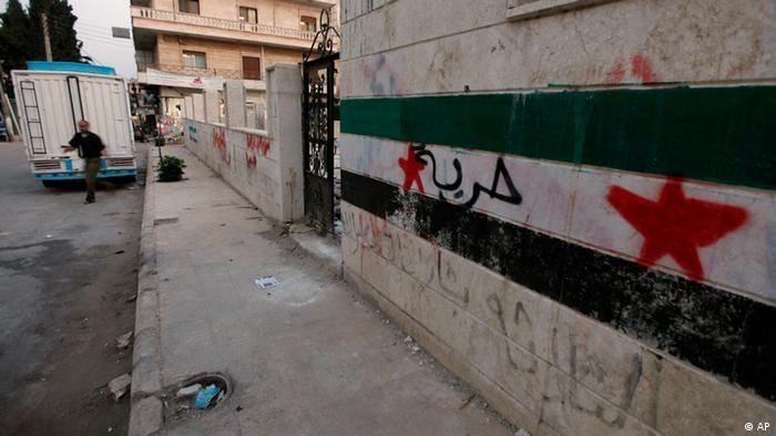 A Syrian man walks next to a wall with the Syrian revolutionary flag painted on it and Arabic writing which reads freedom