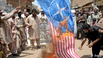 Pakistani protesters burn representations of US and NATO flags during a demonstration to condemn U.S. drone strikes in the tribal areas, in Multan, Pakistan.