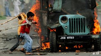 Young Kashmiri boys hit a burning police vehicle after it was set on fire by protestors