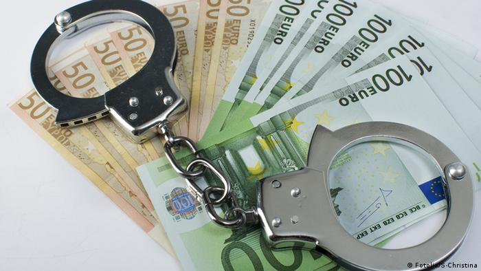 Close-up handcuffs and money over white background. Not isolated. Close-up handcuffs and money © S-Christina #26609805