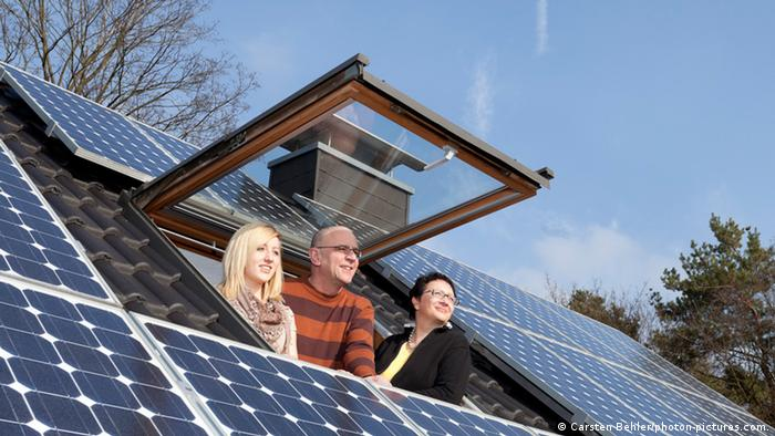 A family and their solar panels on rooftop (photo: Carsten Behler / photon-pictures.com)