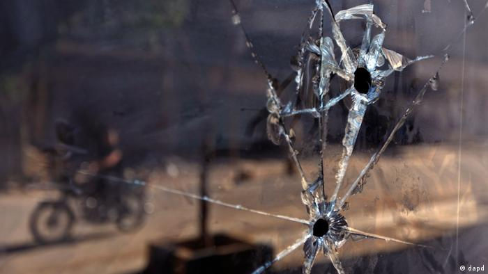 A Syrian man who rides a motorcycle, is seen reflected in a glass door of a shop which has bullet holes, in the town of Taftanaz, 15 kms east of Idleb, Syria, Tuesday, June 5, 2012.