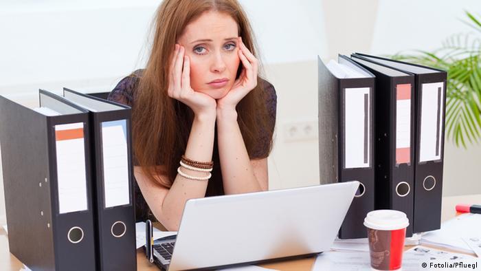 Eine Frau sitzt erschöpft im Büro vor ihrem Computer. Sie hat den Kopf auf die Hände gestützt.