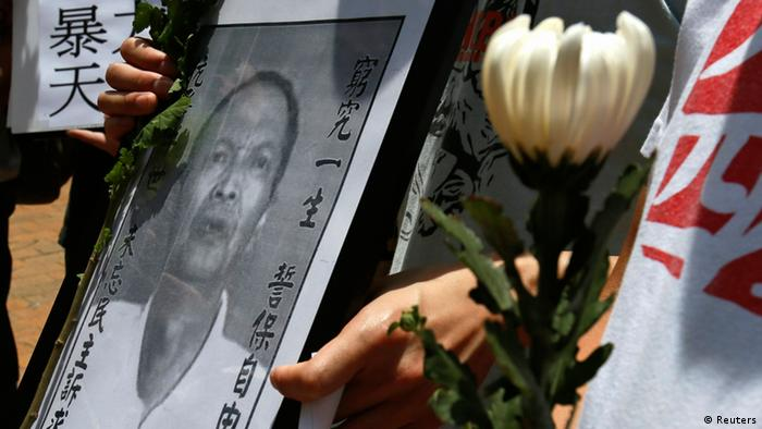 """A protester carries a portrait of Chinese dissident Li Wangyang during a demonstration over his death, in Hong Kong June 7, 2012. Li, a labour activist and Chinese dissident jailed after the 1989 crackdown on pro-democracy protesters in Beijing, was found dead in a hospital ward in central China amidst suspicious circumstances, his family and rights groups said on Wednesday. The Chinese characters on the photograph read, """"To defend the rights of freedom"""". REUTERS/Bobby Yip (CHINA - Tags: CIVIL UNREST POLITICS OBITUARY)"""