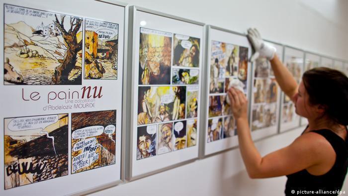 Eine Mitarbeiterin des Comic-Salons reinigt am Mittwoch (06.06.2012) während der Aufbauarbeiten in Erlangen (Mittelfranken) das Glas gerahmter Zeichnungen des marokkanischen Comic-Zeichners Abdelaziz Mouride. Im Rahmen des 15. Internationalen Comic-Salons beleuchtet eine Ausstellung die arabische Comic-Szene. Das wichtigste Festival für grafische Literatur im deutschsprachigen Raum hat noch bis 10. Juni geöffnet. Neben den Klassikern bestimmen längst auch gesellschaftspolitische Themen die grafische Literatur. Foto: Daniel Karmann dpa/lby (zu dpa 0042 vom 07.06.2012)  +++(c) dpa - Bildfunk+++