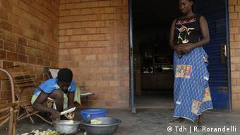 A woman stands next to young girl preparing a meal in Burkina Faso