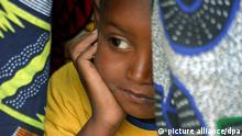 A young Senegalese girl under cover in her mother's traditional clothes, while they attend the official renouncement ceremony of Female Genital Cutting (FGC) at a ceremony in Kidira, eastern Senegal, Sunday 12 March 2006. The town of Kidira on the border with Mali, received representatives from 52 neighbouring villages from Senegal and Mali to publicly announce an end to the practice of Female Genital Cutting (FGC) and early marriage. It was the twentieth renouncement of such harmful practices for girls and women in Senegal. This area has a particularly high rate of FGC since the majority of the ethnic groups living there have practiced these traditions for centuries. One third out of 5,000 Senegalese villages have abandoned FGC since 1997. EPA/PIERRE HOLTZ +++(c) dpa - Bildfunk+++