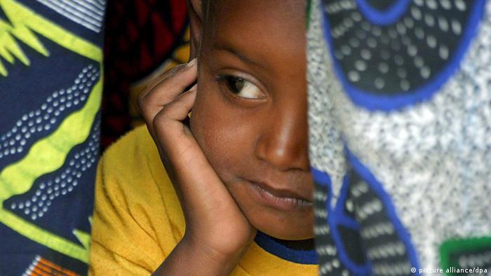 Ein Mädchen guckt unter einer Decke hervor (Foto: EPA/Pierre Holtz)