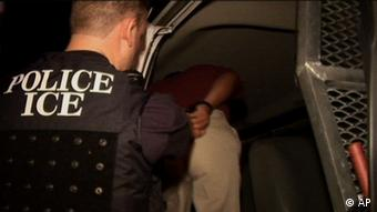 An officer of the federal Immigration and Customs Enforcement agency arrests a suspected undocumented immigrant in Mableton, Georgia