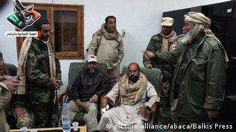A photo made available by Zintan Media Center shows former Libyan leader's son Saif Al Islam Gaddafi, arrested, talking with rebels, in Zintan, Libya on November 21, 2011. Earlier, in a video Saif Al Islam explained wounds on his right hand fingers were one month old, after a NATO raid on his convoy. Photo by Balkis Press/ABACAPRESS.COM # 298676_008