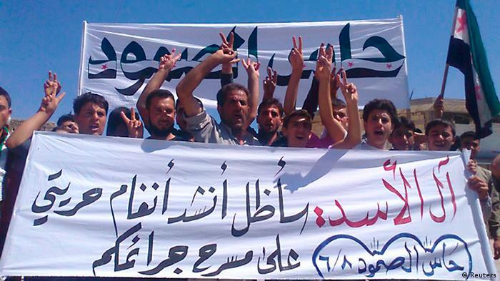 """مراسم تشییع جنازه قربانیان حمص در شمال سوریه در ۸ ژوئن. بر روی پلاکات نوشتهاند: """"خاندان اسد! ما سرود آزادی خود را در نمایش قتلعامهای تو میخوانیم."""""""