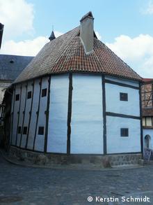 Kleines weißes Fachwerkhaus mit braunen Balken.
