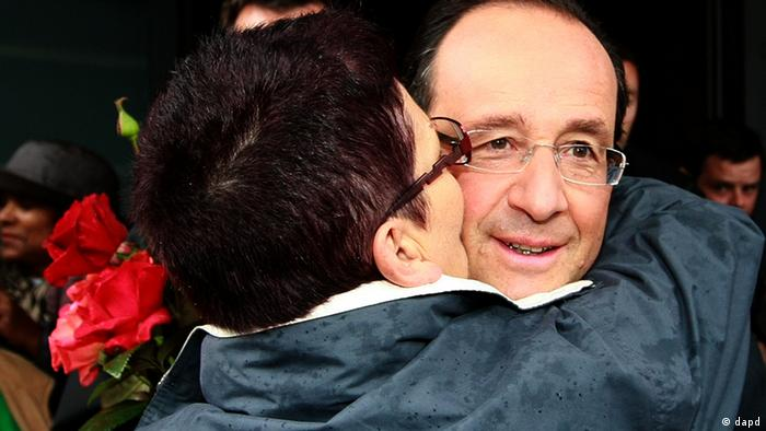 A woman kisses french President Francois Hollande as he leaves the polling station after voting for the first round in the french parliamentary elections in Tulle, central France, Sunday, June 10, 2012. French voters are going to the polls in elections for the lower house of parliament, which will determine whether new President Francois Hollande's Socialists or rival conservatives control the government. (AP Photo/Bob Edme)