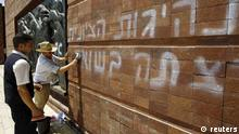 Workers clean graffiti sprayed at Yad Vashem Holocaust memorial in Jerusalem June 11, 2012. Vandals spray-painted anti-Zionist slogans at Israel's Yad Vashem Holocaust memorial and police said on Monday they suspect radical ultra-Orthodox Jews opposed to Israel's existence were responsible. The graffiti reads in Hebrew: The Zionist leadership wanted the Holocaust. REUTERS/Ammar Awad (JERUSALEM - Tags: POLITICS CIVIL UNREST) (eingestellt von qu)