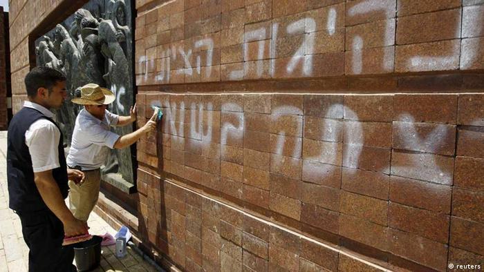 Workers clean graffiti sprayed at Yad Vashem Holocaust memorial in Jerusalem June 11, 2012