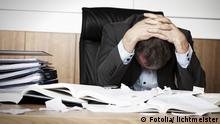 Worried businessman in dark suit sitting at office desk full with books and papers being overloaded with work. Frustrated business person overloaded with work. © lichtmeister #34374491