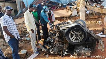 Nigerians look at the remnants of a suicide bombers vehicle at the Christ Chosen Church of God Rukuba following the bomb blast the previous day in Jos, Nigeria, 11 June 2012