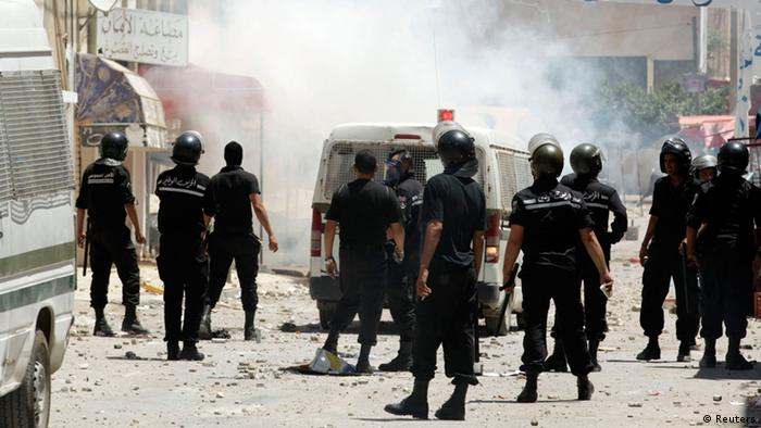 Riot police chase after protesters in Tunis on June 12, 2012.