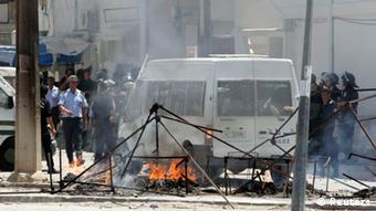 Tunisian riot police near their van and some burning rubble, looking for protestors after Salafists rioted in Tunis in June 2012
