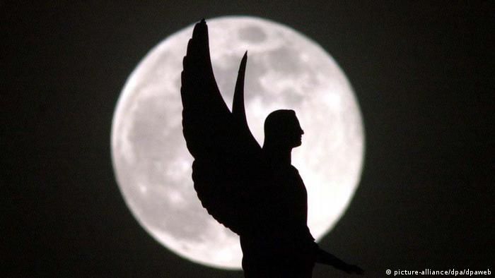Das Bild zeigt die Silhouette eines Engels, der sich auf dem Potsdamer Dom vor dem Vollmond abhebt. dpa (