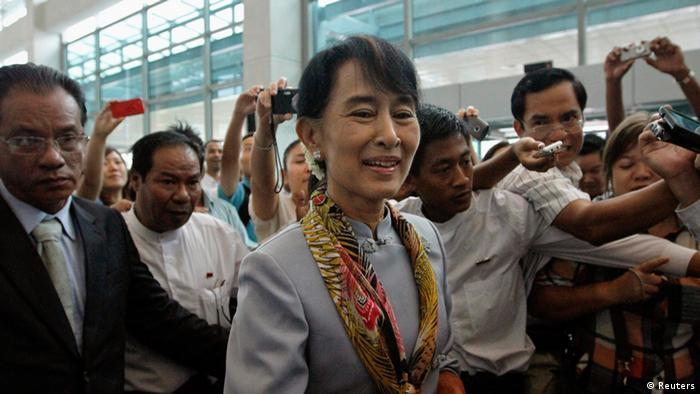 Suu Kyi makes her way through a crowd at Yangon International Airport en route to Europe