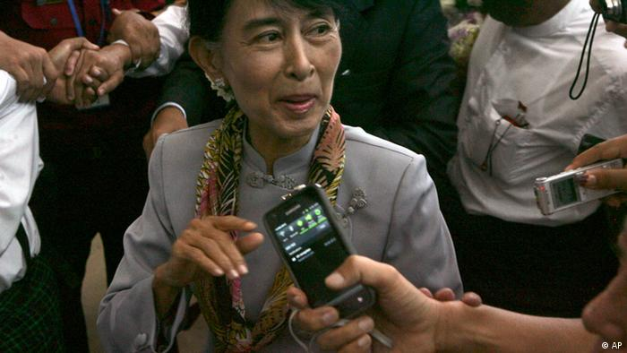 Myanmar opposition Leader Aung San Suu Kyi talks to reporters as she arrives at Yangon International airport