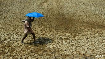 A man walks across dry land holding an umbrella in India