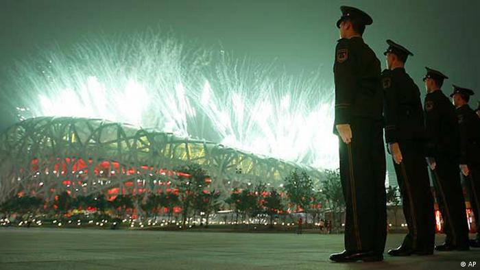 Chinese police stand at attention as fireworks go off during opening ceremony for the Beijing Olympics at the National Stadium at the Beijing 2008 Olympics in Beijing, Friday, Aug. 8, 2008. (AP Photo/Charlie Riedel)