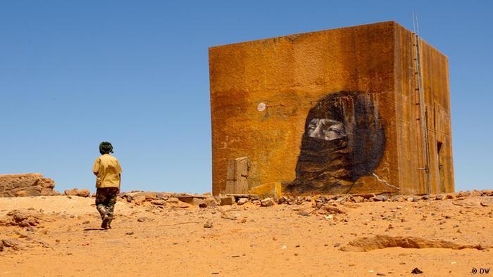 Man walking past a mural in Dajla refugee camp, western Algeria.