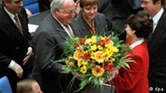 Former chancellor Helmut Kohl (second left) accepts a wreith after being elected chancellor in 1994, as then-FDP leader Klaus Kinkel (right) looks on